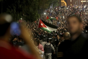 Jordanian protesters raise a national flag during a demonstration outside the prime minister's office in the capital, Amman, on June 4. (Raad Adayleh/AP)